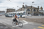 Bicyclist & tram by main train station in Zurich, Switzerland, Europe.