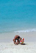 Father and son building sand castle on beach; Curaçao, Netherlands Antilles.