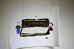 A child's drawing depicting mourners around a dead body in a coffin is displayed on the wall in a room where art therapy classes are held for Syrian refugee children at the Caritas centre in the Bekaa Valley region of Lebanon. The classes form part of the psychological care given to the children to help them overcome the trauma of war using arts, crafts and games.