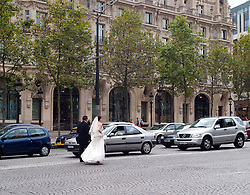 Bride and Groom walk down the center of the Champs Elysees, en route to the  Arch de Triomphe to have their wedding picture taken.