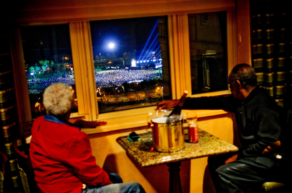 """Obama Election Night in Grant Park, Chicago..Dorothy and James Jackson from Oak Park, Il,  watching from a window at the Hilton Chicago, overlooking the crowds waiting for Obamas victory speech in Grant Park. Mr Jackson says """"It's beautiful. That's all I can say. I never dreamed I would see it""""....Chris Maluszynski /Moment / Agence VU"""