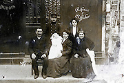 early 1900s group portrait of 3 generation family with new born baby on a Paris street