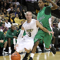 Central Florida guard A.J. Rompza (3) dribbles around Marshall guard Damier Pitts (3) during a Conference USA NCAA basketball game between the Marshall Thundering Herd and the Central Florida Knights at the UCF Arena on January 5, 2011 in Orlando, Florida. Central Florida won the game 65-58 and extended their record to 14-0.  (AP Photo/Alex Menendez)