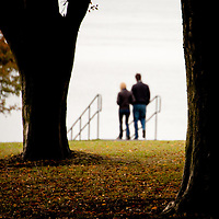 A couple walking through autumn leaves down stairs towards the ocean