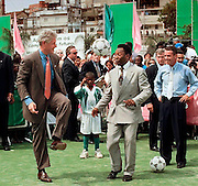 US President Bill Clinton (L) bounces a soccer ball off his knee to Brazilian soccer legend Pele (R) 15 October during a visit to the Mangueira School in the favela of the same name in Rio de Janeiro. Clinton is concluding a three-day official visit to Brazil as part of a one-week-long three-country Latin American tour. (ELECTRONIC IMAGE)