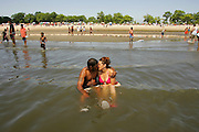 A couple kiss as they sit in the water at Orchard Beach in the Bronx.