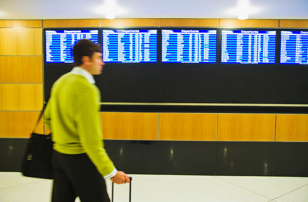 A businessman walking in front of the departures board in an airport with his luggage.