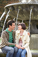 Embracing couple sitting on edge of fountain