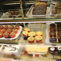 Deserts are shown in the display case by the counter.