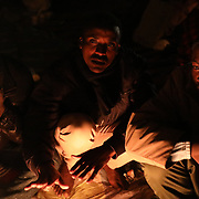 Migrants mostly from the Darfur region of western Sudan warm up by a fire under a highway bypass where they have been sheltering from the weather as they prepare to attempt to cross the Italian border into France, in the Mediterranean coastal town of Ventimiglia, northern Italy.