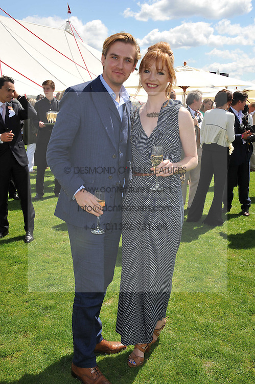DAN STEVENS and his wife SUSIE at the 27th annual Cartier International Polo Day featuring the 100th Coronation Cup between England and Brazil held at Guards Polo Club, Windsor Great Park, Berkshire on 24th July 2011.