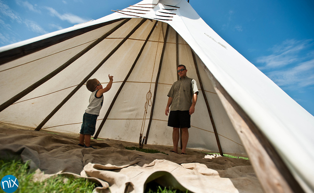 THomas Broome, 2, and his father Jason Broome, of Charlotte, check out the inside of a tee pee set up at the Frank Liske Park Powwow Saturday afternoon.  (photo by James NIx)