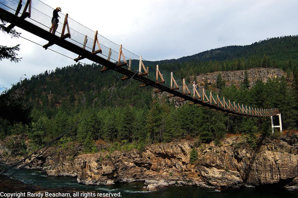 Ladies stainding on Swinging Bridge over the Kootenai River. Lincoln County, northwest Montana
