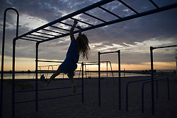 Girl swinging on monkey bars at park on beach at dusk