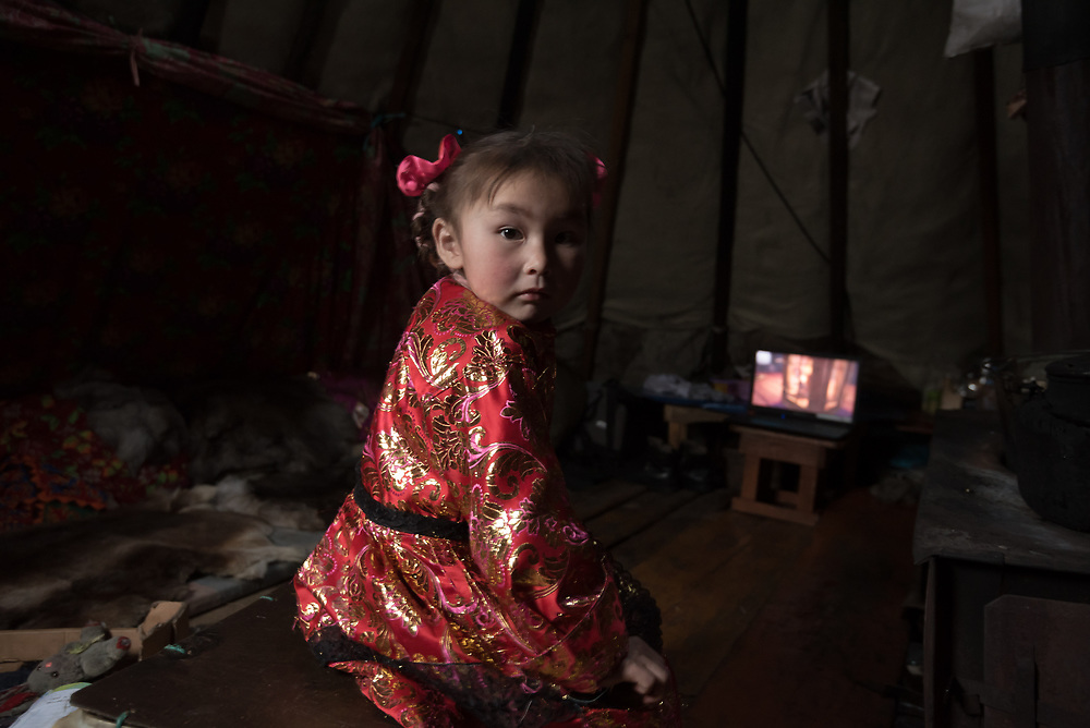 Christina, a young Nenets girl, inside the family chum watching a DVD on a laptop computer.