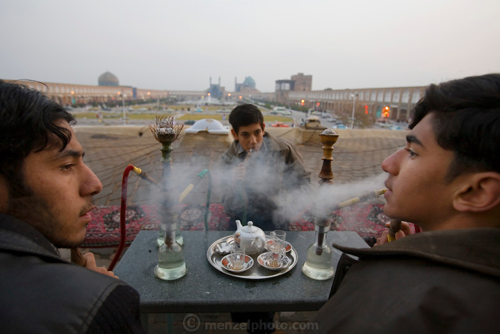 15-year olds smoke water pipes (hookahs) in a tea shop overlooking Imam Square, Isfahan, Iran. In the distance, a view of the magnificently tiled Masjed-e Imam (Royal Mosque)  built by the Safavid ruler, Shah Abbas 1, as part of the renovation of the central square of Isfahan.