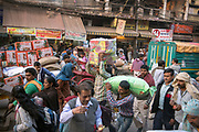 Workers and shoppers crowd the streets in Chandni Chowk, Old Delhi, India.