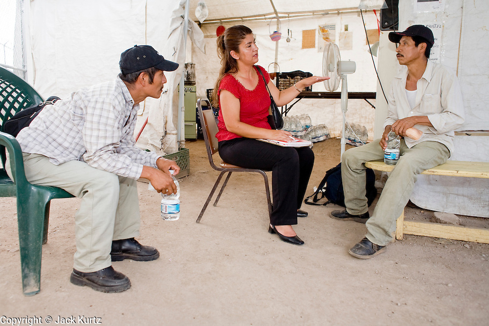16 JULY 2007 -- NOGALES, SONORA, MEXICO: SILVIA GONZALEZ, a social worker from the Mexican state of Sonora, talks to immigrants from the Mexican state of Oaxaca who had been deported from the United States at the No More Deaths aid station near the Mexican port of entry in Nogales, Sonora, Mexico. No More Deaths and the Sonora state government set up the aid station in 2006 to help Mexican immigrants deported from the US from across the US Border Patrol station in Nogales, Arizona. Volunteers at the aid station provide immigrants, many of whom spend days in the desert before being apprehended by the US Border Patrol, with food and water and rudimentary first aid. The immigrants then go back to their homes in Mexico or into Nogales to make another effort at crossing the border. Volunteers said they help between 600 and 1,000 immigrants per day. The program costs about .60¢ per person to operate. So far this year they've helped more than 130,000 people.  Photo by Jack Kurtz