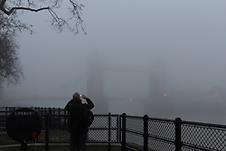 © Licensed to London News Pictures. 30/12/2016. LONDON, UK.  A tourist takes a photograph of Tower Bridge on the River Thames, which is shrouded in fog. London is experiencing more freezing and foggy weather this morning.  Photo credit: Vickie Flores/LNP