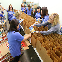 Junior Auxiliary of Tupelo members fill bags with snacks as part of their Silent Servings program on Friday morning in Tupelo. The Silent Servings bags are for area students lacking nutritional support at home and are packed every two weeks then picked up by a school employee and also delivered to the schools by a Junior Auxiliary member. The program allows the students to have snack over the weekend that they may otherwise not get.