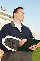 Coach with clipboard by running track