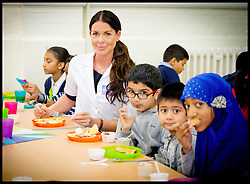 Image ©Licensed to i-Images Picture Agency. 20/06/2014. London, United Kingdom. TV Doctor Anita Sturnham serves up breakfast and gives a lesson in nutrition to pupils at the Breakfast Club at Mayflower Primary School, East London, as part of the Mayor's Fund Bigger Breakfast Campaign. Picture by Andrew Parsons / i-Images