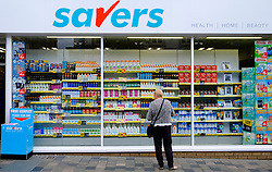 Woman window shopping in budget shop  Savers, in Glasgow Scotland United Kingdom