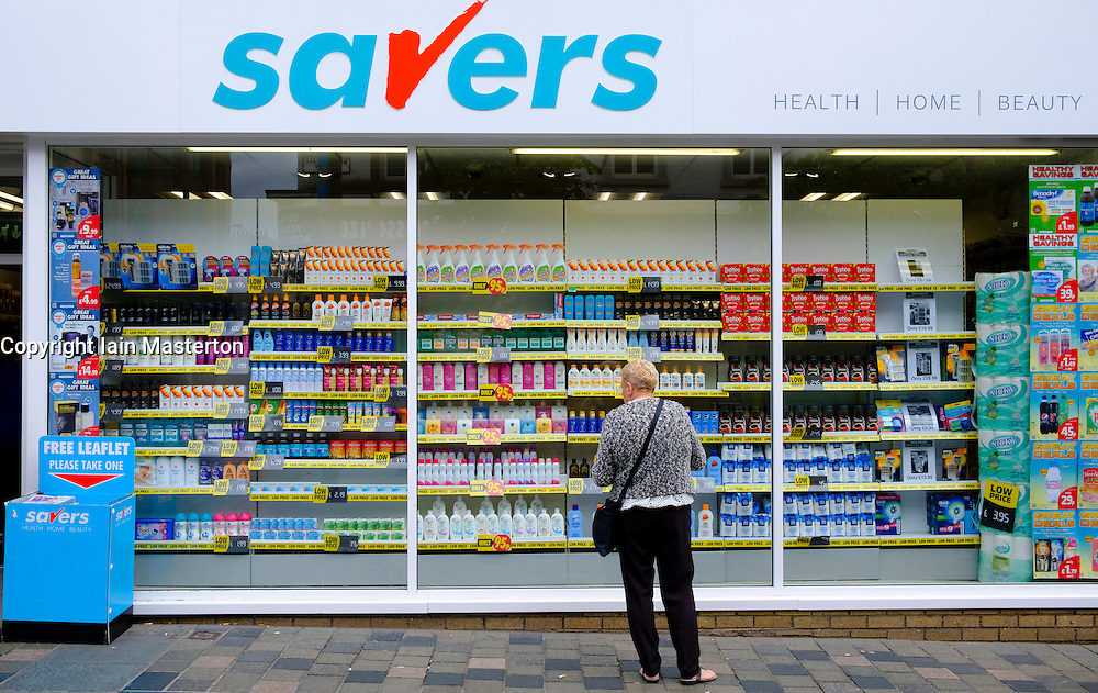 Woman window shopping in budget shop  Savers, in Glasgow Scotland United Kingdom