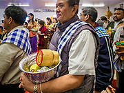 14 APRIL 2019 - DES MOINES, IOWA: Men line up to make an offering in the Tak Bat during Lao New Year, also called Songkran,  observances at Wat Lao Buddhavath in Des Moines. Several thousand Lao people live in Des Moines. Most came to the US after the wars in Southeast Asia. Songkran is celebrated in Theravada Buddhist countries (Sri Lanka, Myanmar, Thailand, Laos, and Cambodia) and in Theravada Buddhist communities around the world.        PHOTO BY JACK KURTZ