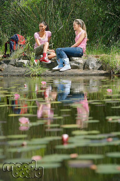 Young Women Sitting by Creek