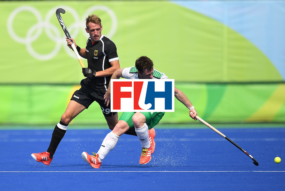 Germany's Niklas Wellen vies for the ball with Ireland's John Jackson during the men's field hockey Germany vs Ireland match of the Rio 2016 Olympics Games at the Olympic Hockey Centre in Rio de Janeiro on August, 9 2016. / AFP / MANAN VATSYAYANA        (Photo credit should read MANAN VATSYAYANA/AFP/Getty Images)