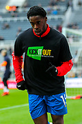 Jeffrey Schlupp (#15) of Crystal Palace warms up wearing a 'Kick It Out' campaign t-shirt ahead of the Premier League match between Newcastle United and Crystal Palace at St. James's Park, Newcastle, England on 6 April 2019.