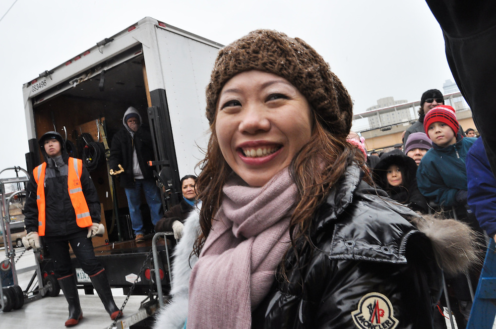 """A woman in the crow smiles as an unidentifiable male on the Chinese New Year Parade grandstand pulls a """"Joe Biden"""" and unwittingly utters profanities into a live microphone broadcasted over amplifiers for all parade goes to hear; Chinatown, February 6th, 2011"""