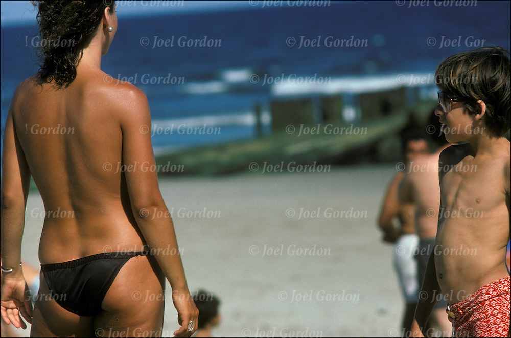 Exhibitionism voyeurism - nude beach - boy looking at topless woman