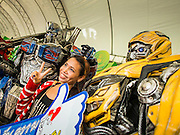 "24 JULY 2014 - BANGKOK, THAILAND:  A Thai woman poses for selfies with characters inspired by the Transformer movies at the happiness party in Bangkok. The Thai Junta is organizing a series of public events throughout Thailand meant to bolster public opinion. The events are called ""restoring happiness to the people"" parties. They feature historic pageants, music, food, health checks and free haircuts. The party in Bangkok is on Sanam Luang, the Royal Parade Ground, which is near the Grand Palace and the Ministry of Defense.   PHOTO BY JACK KURTZ"