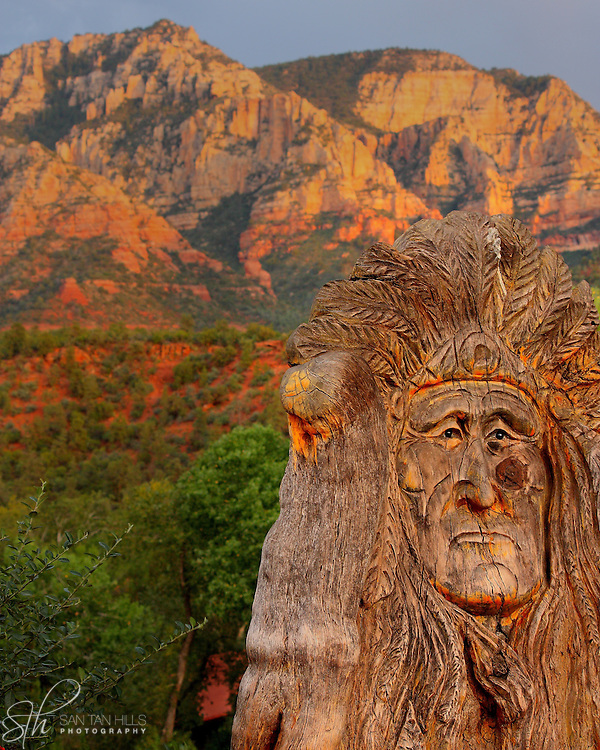 Wood carving of an American Indian stands before the majestic red rocks of Sedona