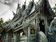"03 APRIL 2016 - CHIANG MAI, THAILAND: The ubosot, or ordination hall, of Wat Sri Suphan. Wat Sri Suphan is also known as the ""Silver Temple"" because of its silver ubosot, or ordination hall. The temple is more than 500 years old but the silver ordination hall was recently remodeled. The ordination hall is covered in silver and the interior is completely done in silver and gold. It's traditionally served as the main temple for the silversmiths of Chiang Mai, whose community is around the temple.     PHOTO BY JACK KURTZ"