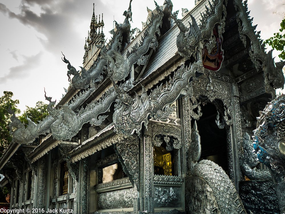 """03 APRIL 2016 - CHIANG MAI, THAILAND: The ubosot, or ordination hall, of Wat Sri Suphan. Wat Sri Suphan is also known as the """"Silver Temple"""" because of its silver ubosot, or ordination hall. The temple is more than 500 years old but the silver ordination hall was recently remodeled. The ordination hall is covered in silver and the interior is completely done in silver and gold. It's traditionally served as the main temple for the silversmiths of Chiang Mai, whose community is around the temple.     PHOTO BY JACK KURTZ"""