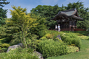 Richmond Upon Thames, London, England, UK, July 7 2018 - Japanese Gateway and Japanses garden at Kew gardens. The Gateway was built for the Japan-British Exhibition (1910) and moved to Kew in 1911. It is a four-fifths scale replica of the karamon (gateway) of the Nishi Hongan-ji temple in Kyoto<br /> Kew Gardens (or Royal Botanical Gardens, Kew) is a botanical garden in southwest London. It is one of London's top tourist attractions and is a World Heritage Site. The site of 121 hectares opened in 1759 and houses more than 30,000 different kinds of plants and 40 listed buildings and structures, including the world's greatest glasshouse.