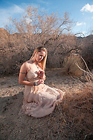 Young woman in a beautiful dress kneeling in a secluded desert landscape.