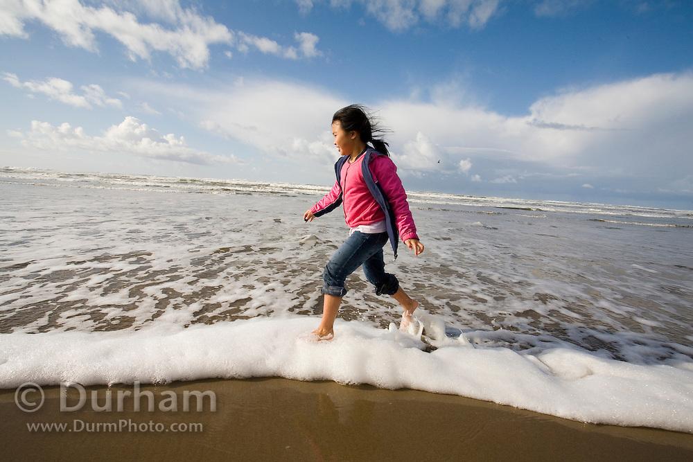 Nine year old Vira Halim-Rotinsulu runs in the surf on the beach at the Oregon Coast.
