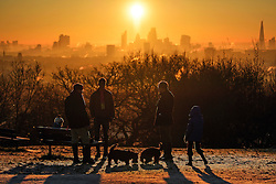 © Licensed to London News Pictures. 29/12/2016. London, UK. A group of dog walkers stop on Parliament Hill on Hampstead Heath London to watch the sunrise over the city of London on another cold winter morning. Most of the UK has woken to freezing temperatures. Photo credit: Ben Cawthra/LNP