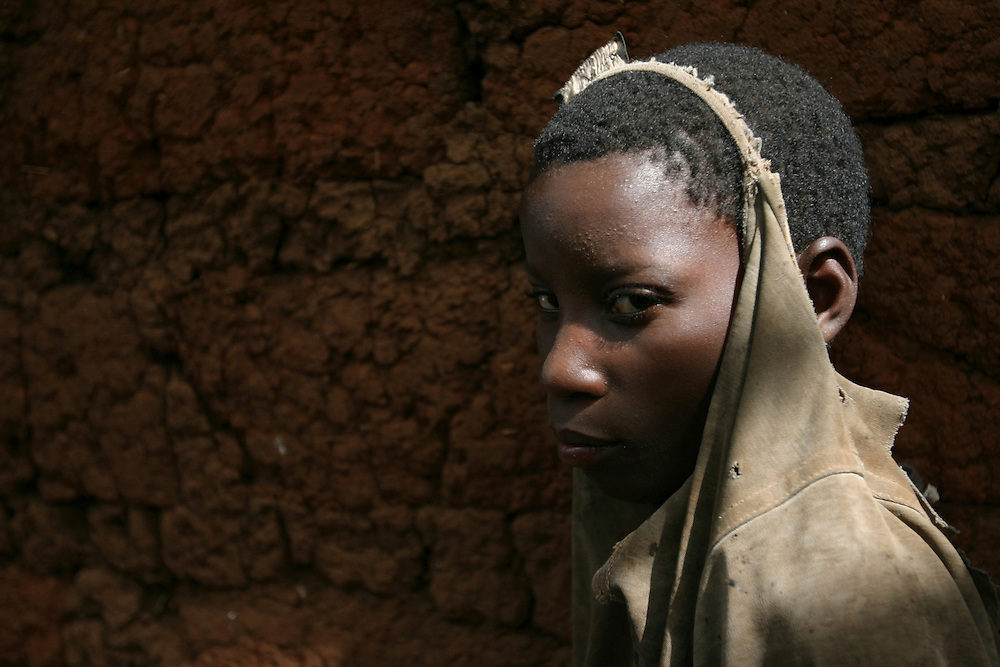 Young boy living in the countryside in Burundi in Africa in a poor surrounding standing near his mud house during rainy season. @ Martine Perret. 24 Octobre 2005