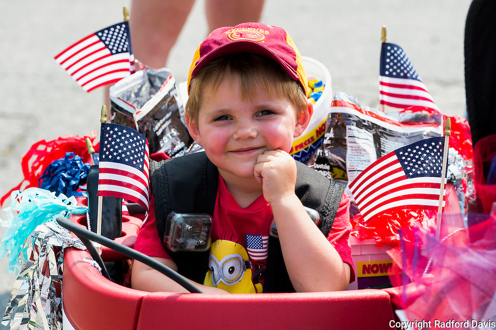Boy in a red wagon at the Fourth of July parade in Ames, Iowa