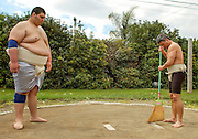 Amateur sumo heavyweight Steve Jimenez (L) looks on as lightweight Brian Condon (R) smoothes a backyard dohyo surface between matches at the Shunbun 2006 tournament in Garden Grove, CA, March 19, 2006.  The 'Dohyo of Dreams' was built in 1997 by homeowner/sumo enthusiast Jim Lowerre to provide a practice and competition space for the amateur sumo association Southern California Sumo Kyokai.