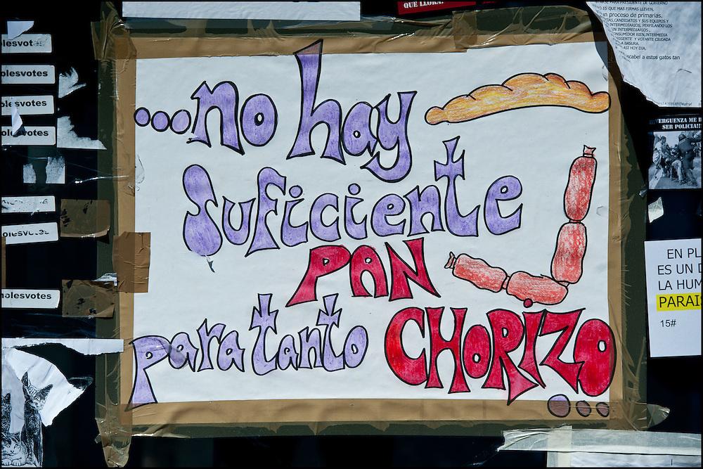 """Une affiche aux abords du campement place Puerta del Sol. // Le mouvement spontane du """"15 M"""" (15 mai) compose de citoyens espagnols campe depuis 2 semaines sur la place Puerta Del Sol avec pour revendication la construction d'une democratie nouvelle. Organise en commission les citoyens prennent la parole lors d'assemblee ouverte a tous - Place Puerta Del Sol à Madrid le Juin 2011. ©Benjamin Girette/IP3Press"""