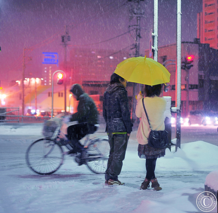 A Japanese couple standing in the snow sheltered from the cold and snow by an umbrella and their warm love. A lone biker rides past on his bicycle.