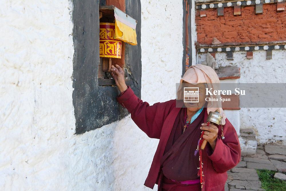 Pilgrim spinning praying wheels at Jambay Lhakhang, Bumthang, Bhutan
