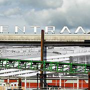 """Nederland Rotterdam 3 september 2007 20070903 ..Voorbereidingen voor het verwisselen van de letters op het dak van het centraal station; ipv centraal station zal binnenkort """" traan laten """" te lezen zijn, ivm de sloop van CS Rotterdam ."""" Het doek is gevallen """" Zondag 2 september is het doek letterlijk doek gevallen voor het in 1957 geopende gebouw. Over enkele weken wordt de schepping van architect Sybold van Ravesteyn gesloopt en komt op het Stationsplein een nieuwe OV-terminal, die na 2011 ruim 300.000 reizigers per dag moet kunnen verwerken. Voorbijgangers maken een foto van het oude bekende centraal station, dat sinds 1957 dienst heeft gedaan. Een gloednieuw station zal op deze plek verrijzen. ..Het tijdelijke station dat de periode overbrugt tussen de sloop van het oude Rotterdam CS en de bouw van een nieuw station, kost 12 miljoen euro. Dat is een schijntje vergeleken met het half miljard waarop het nieuwe is begroot. De bedoeling is dat de tijdelijke bebouwing in februari klaar is. Het blijft open tot 2010. Het oude gebouw maakt plaats voor vijf tijdelijke. Daarvan zijn er vier voor de reizigers en een voor het personeel van de Spoorwegpolitie. ..Tijdelijk Rotterdam Centraal.1 september 2007..Alle treinreizigers opgelet! Vanaf 2 september sta je voor een dichte deur als je bij Rotterdam Centraal op de trein wilt stappen. Tenzij je de ingang van het tijdelijke Rotterdam Centraal al gevonden hebt. ..Naast het oude vertrouwde station staat al een tijdje een groot blauw gebouw en vanaf 2 september kun je daar op je trein stappen. Je kunt er zelfs een kopje koffie halen, of kleine boodschappen doen. Alle winkels zijn namelijk gewoon verplaatst naar het grootste tijdelijke station van Nederland...Het Centraal Station was al een hele tijd een grote bouwput, want er wordt heel hard gewerkt aan een nieuw, beter en vooral moderner station. Maar omdat afscheid nemen altijd zo moeilijk is, vindt er op 12 september een soort ode aan het station en de architect Sybold van R"""