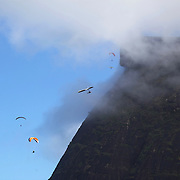 Hang gliders and para gliders flying above the hillside of Pedro Bonita high in the hills of Rio de Janeiro. Pilots of hang gliders and para gliders take tourists for tandem flights with breathtaking views of the city before landing on Sao Conrado beach. Rio de Janeiro,  Brazil. 9th September 2010. Photo Tim Clayton.